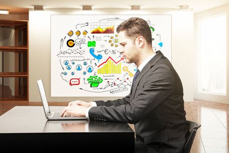 sketch: Side view of young businessman using laptop in sunlit office interior with business drawings on banner. Technology concept. 3D Rendering Stock Photo