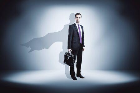 Businessman with super hero cape shadow in concrete interior. Leadership concept
