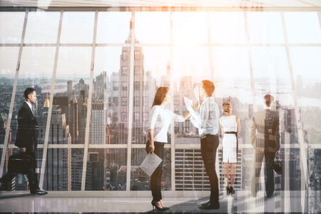 Businesspeople dealing with paperwork in modern concrete interior with New York city view. Team work concept. Double exposure Stock Photo