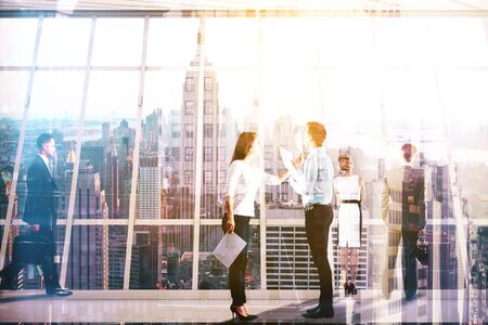 Businesspeople dealing with paperwork in modern concrete interior with New York city view. Coworking concept. Double exposure