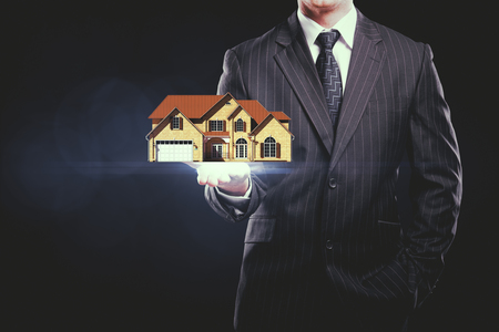 front house: Businessman holding abstract house miniature on dark background. Real estate concept