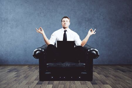 meditation man: Meditating businessman with laptop sitting on armchair in interior with concrete wall and wooden floor. Relaxation concept. 3D Rendering