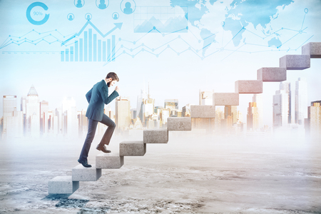 Side view of young businessman climbing concrete stairs in abstract city background with creative business charts. Success concept. Double exposure