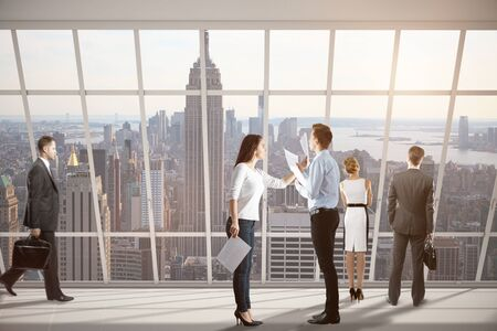 Businesspeople dealing with paperwork in modern concrete interior with New York city view. Teamwork concept. 3D Rendering