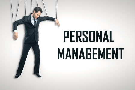 Businessman puppet on light background with text. Personnel management concept Stock Photo