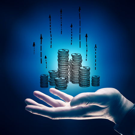 close up: Side view of businessmans hand holding drawn coins with upward arrows on blue background. Financial growth concept