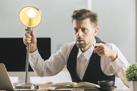 Hombre de negocios loco con la lámpara que interroga a alguien en el escritorio con la taza de café, la computadora portátil, las fuentes y otros artículos