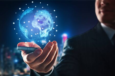 creative: Blurry businessman holding cellphone with abstract polygonal globe on night citgy background. Network concept. 3D Rendering