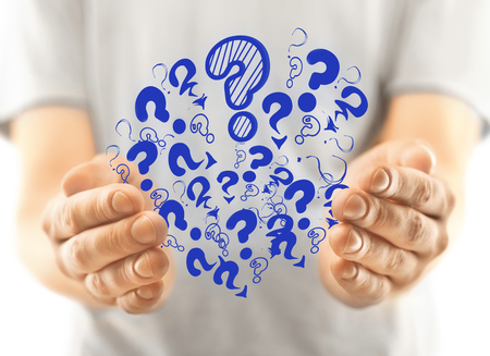 Blurry mans hands holding abstract drawn blue question marks. FAQ concept