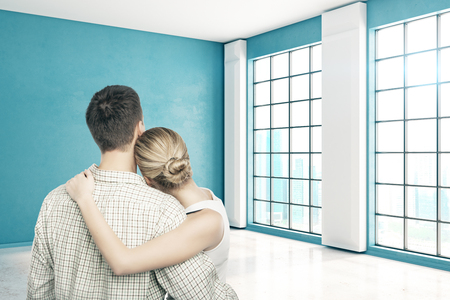 Back view of young european couple standing in empty blue interior with city view and sunlight. Moving concept. 3D Rendering photo
