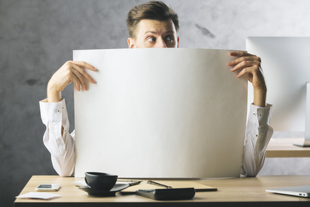 Surprised businessman covering face with huge empty paper sheet. Mock up Stock Photo