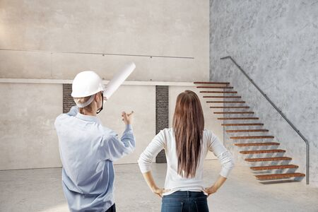discussing: Back view of male worker and woman in loft interior with stairs. Design and architecture concept. 3D Rendering Stock Photo