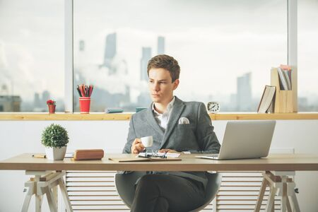 cup: Attractive caucasian guy drinking coffee and using laptop in modern office with blurry city view and items on desktop