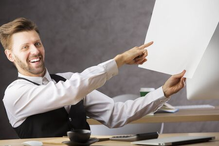 working office: Smiling businessman pointing at big paper sheet in his office. Engineering architectural project concept Stock Photo
