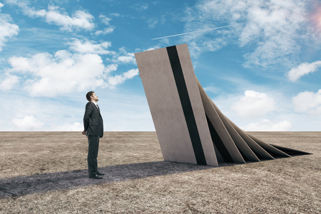 Uomo d'affari premuroso con enormi carte di credito a cadere su di lui nel deserto con cielo blu e luce del sole. Concetto di crisi. Rendering 3D