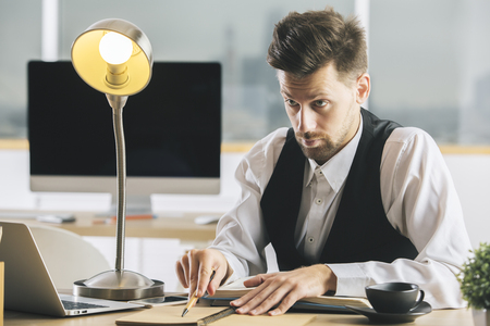 Crazy man with lamp interrogating someone at desk with coffee cup, laptop, supplies and other items Stock Photo