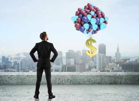Back view of young businessman on concrete rooftop looking at balloons with golden dollar sign on city background. Profit concept. 3D Rendering
