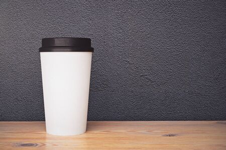 Empty white take away coffee cup placed on wooden surface and textured concrete wall background. Ad concept. Mock up, 3D Rendering