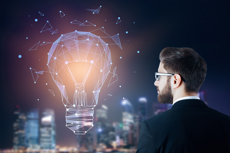 creative: Side portrait of young businessman looking at abstract polygonal lamp on night city background. Technology and innovation concept. Double exposure