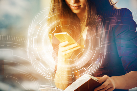 Attractive young woman using smartphone and holding open book on blurry background with digital business buttons. Innovation concept. Double exposure