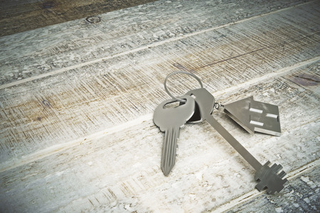 real estate house: Top view of metal keys with house keychain placed on aged wooden background. Real estate concept. 3D Rendering Stock Photo