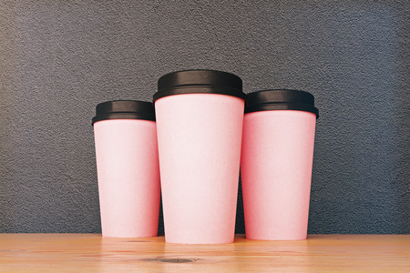 cup: Three pink empty take out coffee cups placed on shiny wooden surface and grainy concrete wall background. Drink, breakfast advertising concept. Mock up, 3D Rendering