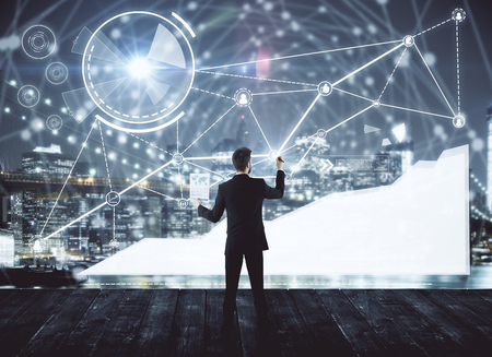 Back view of young businessman drawing abstract glowing digital business hologram on wooden pier with night city view. Technology, innovation and network concept. Double exposure