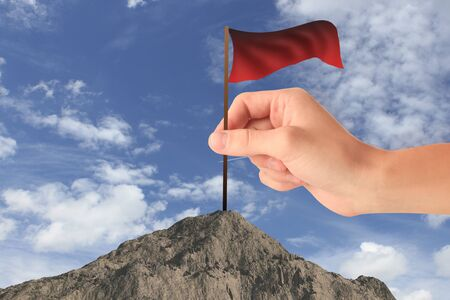 Hand placing waving red flag on mountain top. Sky background. Win concept