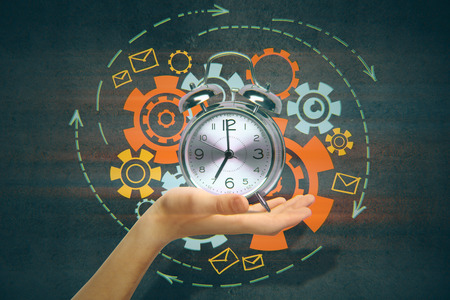 silver background: Hand holding silver alarm clock with abstract cogwheel sketch. Time management concept