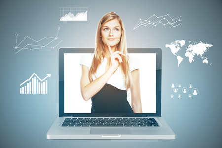 Thoughtful young woman inside laptop screen on gray background with business charts. Online finance concept photo