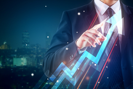 Businessman pointing at abstract upward chart arrow on night city background. Finance concept. Double exposure