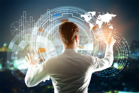 Back view of young businessman managing digital business buttons on night city background. Technology and infograph concept. Double exposure