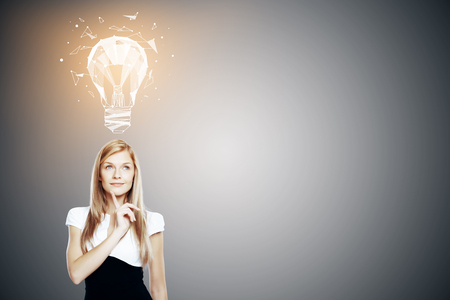 Portrait of attractive thoughtful young woman with glowing polygonal lamp above head on gray background with copy space. Imagination and idea concept photo