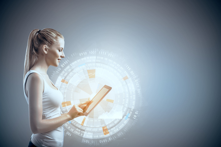 Side portrait of young woman using tablet with business hologram. Innovation and communication concept photo