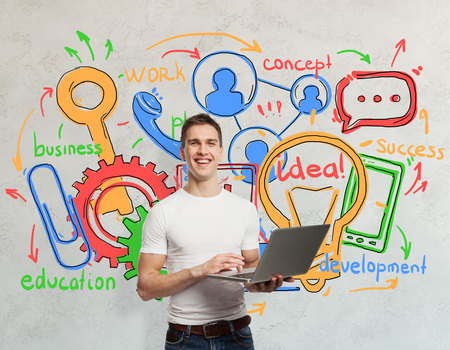 Happy young man holding laptop on concrete wall background with colorful business drawings. Technology and communication concept photo