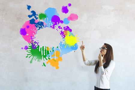 Mujer joven pensativa que señala en bosquejo colorido abstracto en la pared de cemento. Concepto de tormenta de ideas