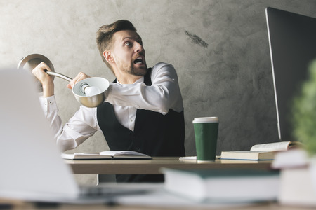 banana: Lunatic businessman about to break computer monitor with lamp while sitting at desk with coffee cup, books and other blurry items Stock Photo