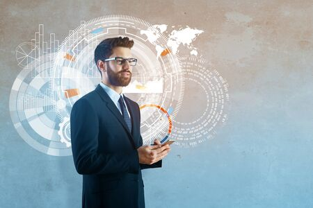 display: Businessman holding smartphone with abstract business hologram on concrete wall background. Technology and communication concept