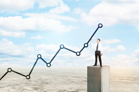 Young businessman standing on concrete block in desert and drawing upward chart line on sky background. Income concept photo