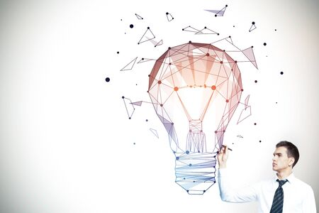 Young businessman drawing abstract polygonal lamp on gray background. Imagination, technology and idea concept. 3D Rendering photo