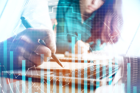 Close up of businesspeople doing paperwork on office desktop with laptop and abstract business chart. Accounting and analytics concept. Double exposure Archivio Fotografico