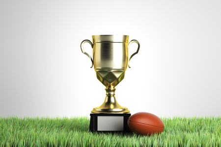 Golden winners cup with rugby ball placed on grass. Gray background with copy space. Championship concept. 3D Rendering Stock Photo