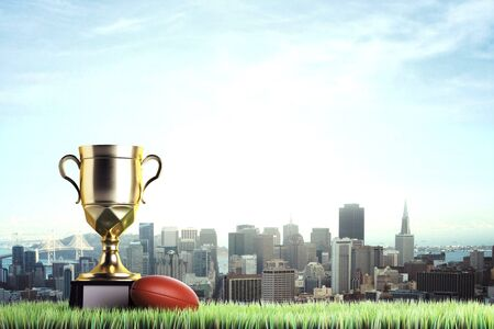 Golden winners cup with rugby ball placed on grass. City background with copy space. Competition concept. 3D Rendering