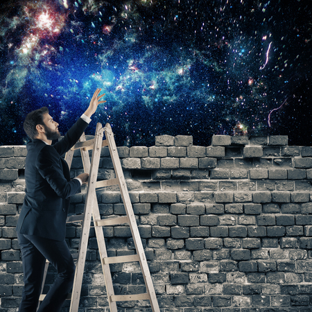 Young businessman on ladder looking at universe from behind brick wall. Explore concept