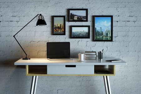 comfortable: Close up of creative designer desk with blank laptop, coffee cup, lamp, picture frames and other items on white brick wall background. Mock up, 3D Rendering