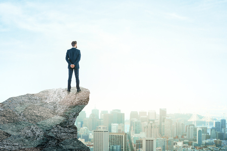 Back view of young businessman on mountain top looking at city with daylight. Future concept. Copy space Stock Photo