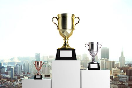rendering: Golden, silver and bronze winners cups placed on white pedestals. City background. Prize concept. Mock up, 3D Rendering