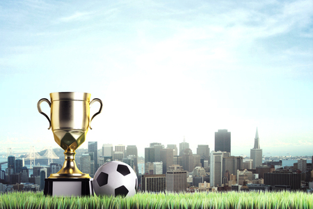 Golden winners cup with football placed on grass. City background with copy space. Honor concept. 3D Rendering