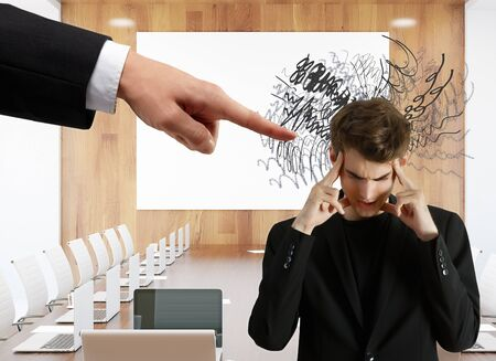 ceo: Hand pointing at pensive businessman with scribble. Meeting room background. Stress concept