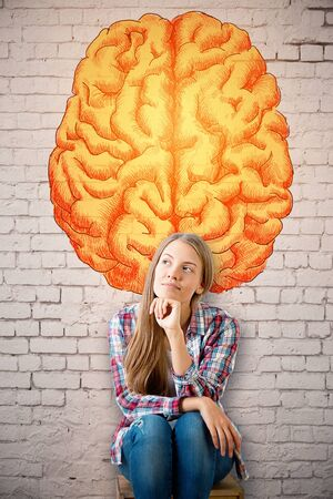 Thoughtful young european woman on brick wall background with creative brain sketch. Brainstorming concept Stock Photo